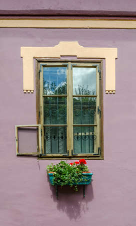Old medieval window from a house with an exterior opening on a beautiful violet wall with a flower pot