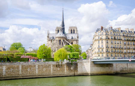 Notre Dame de Paris Catholic Christian Cathedral with the Seine river, a bridge and typical parisian buildings on a sunny spring day