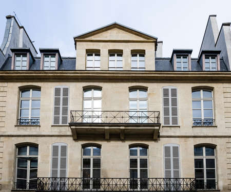 Generic historic building in Paris, France, with beautiful balconets, balconies and dormer windows at the attic with a contrast processing