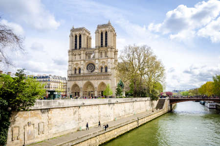 Notre Dame de Paris Cathedral on de Ile de la Cite in the beautiful European city with the Seine river flowing on the right and many tourists visiting the monument