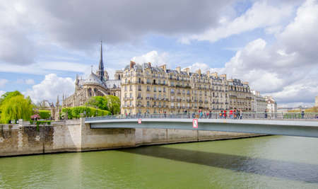 Paris, France: The Seine river in Paris with a bridge full of tourists and The Notre Dame de Paris gothic catholic Cathedral and other french buildings on a sunny spring day