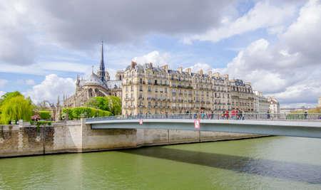 Paris, Frankreich: Die Seine in Paris mit einer Brücke voller Touristen und der gotischen katholischen Kathedrale Notre Dame de Paris und anderen französischen Gebäuden an einem sonnigen Frühlingstag Standard-Bild