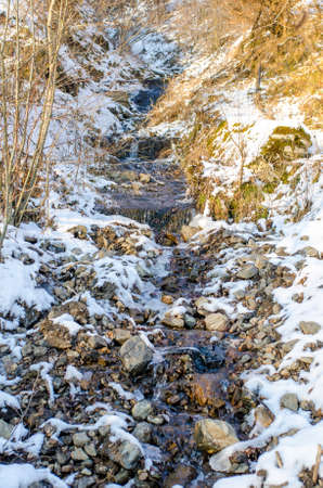 Mountain stream running on a cold sunny winter day with snow and ice all over