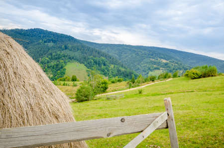 Rural countryside view with a hay stack and wood fence in the front and a forest on the mountain on the back