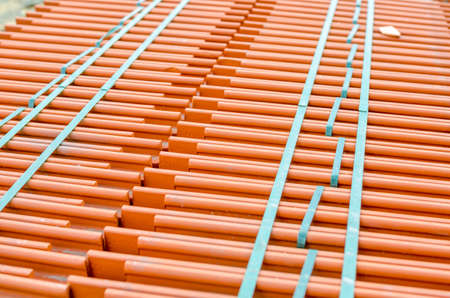 Roof shingles with a bright orange color on a construction site awaiting to be put into place