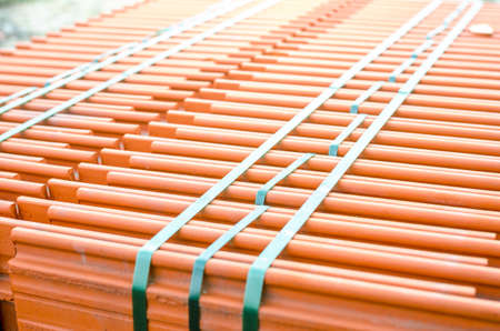 Roof tiles in a stack on a construction site or a deposit awaiting to be put onto a house roof Stock Photo