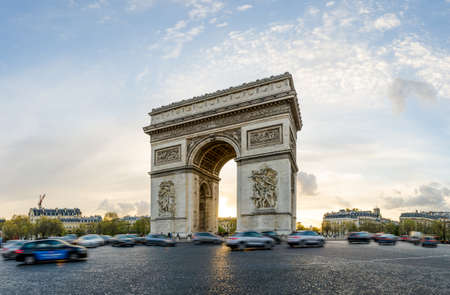 The Arch of Triumph in Paris, France on a sunny spring sunset with cars moving all arond the intersection at this beautiful landmark