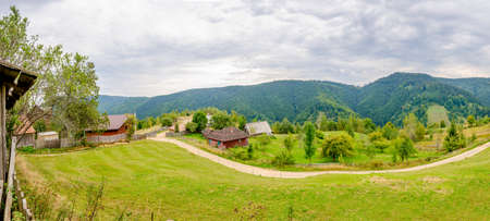 Wide perspective from a peak next to some rural cabins in Transylvania region of Romania wth the forest in the distance