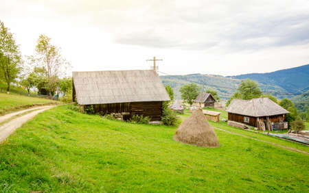 Small old village on the mountain in a Transylvanian rural area with wooden houses and a beautiful vibrant green pasture Standard-Bild