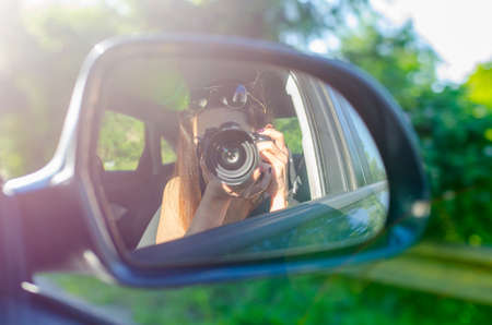 A beautiful woman taking a picture with a profesional dslr camera on a fats moving car in the rear view mirror trying to become a photographer