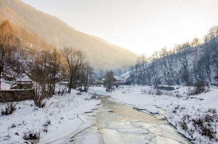 A frozen stream running through a rural village in the Transylvania countryside on a cold winter day Standard-Bild