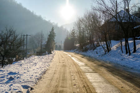 Rural road on a sunny winter day with snow all over the path and trees in Transylvania