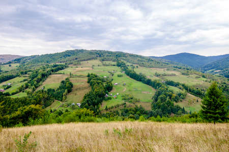 Beautiful view of a Transylvanian rural village spread on a hill with a lot of trees and mountains on the background