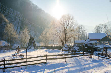 Snow all over a rural village and forest with a wooden fence and a house on the background on a bright sunny day