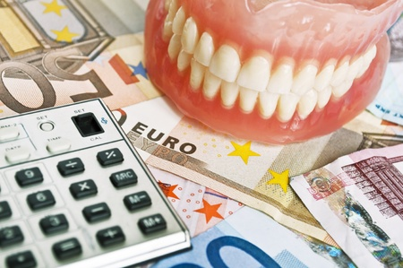 Denture and calculator on euro bank notes photo
