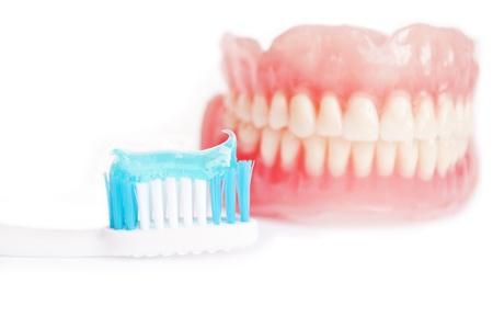 molares: Dentadura postiza y cepillo de dientes con pasta de dientes aislados en blanco