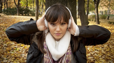 Close-up of a beautiful woman listening music outdoor photo