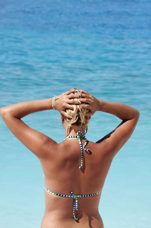 Young woman in blue bikini standing on sand beach and looking at sea  photo