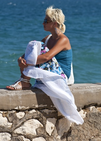 Beautiful blond girl enjoying sun near sea  photo