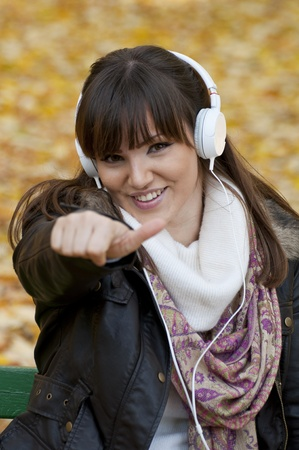 Portrait of a beautiful smiling woman listening to music with thumb up photo