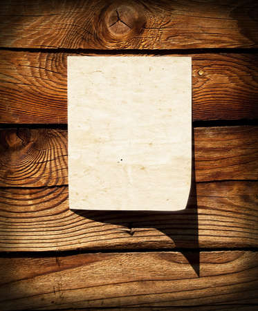 Empty grunge paper on wooden wall photo