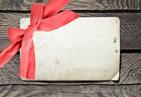 Grunge empty card and red bow on wood background photo