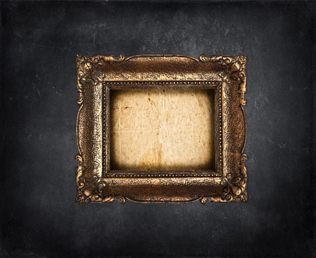 Empty golden frame on black grunge wall photo