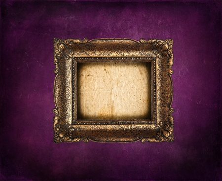 Empty golden frame on purple grunge wall photo