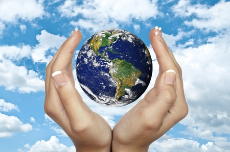 Human hands holding planet Earth against blue sky - Environmental protection concept photo