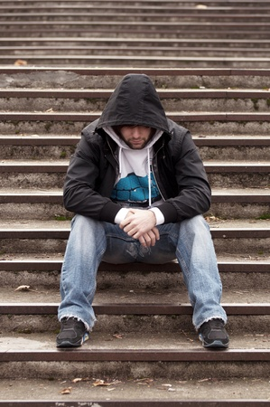 Sad teenage boy with hood sitting on stairs photo