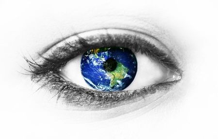 Planet earth in eye isolated on white photo