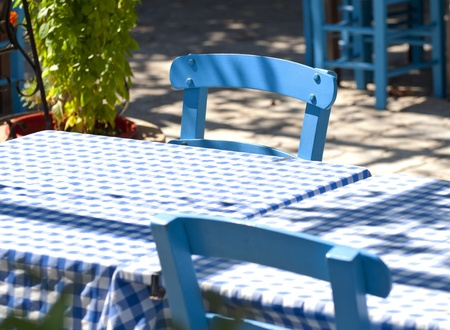 Detail of traditional Greek tavern blue tables and chairs photo