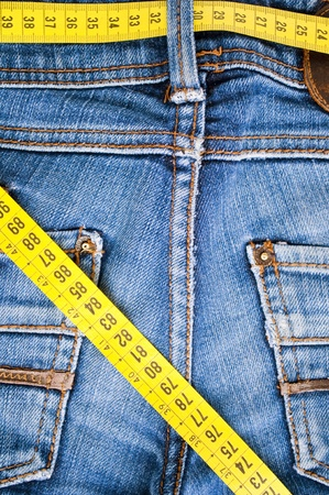 tight jeans: Blue jeans and measure tape - concept of overweight  Stock Photo
