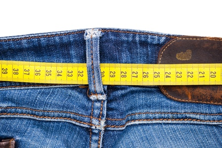 Blue jeans and measure tape isolated - concept of overweight  photo