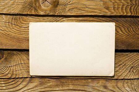 Grunge note paper on wooden background  photo