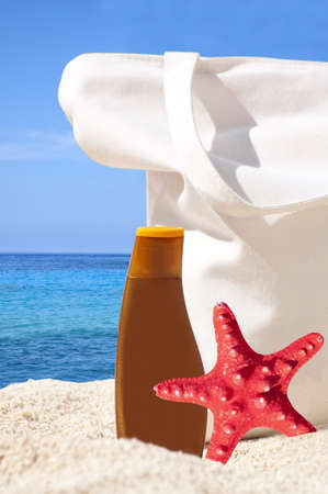 Beach bag, sun cream and starfish on tropical beach - Holiday concept  photo
