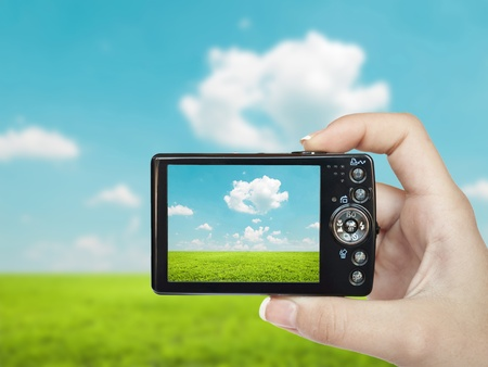 Hand holding digital camera and making landscape photograph photo