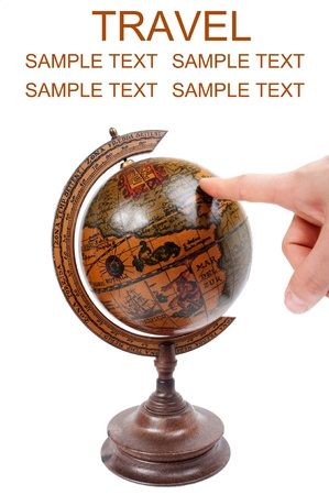 Hand pointing to antique globe - Travel concept photo
