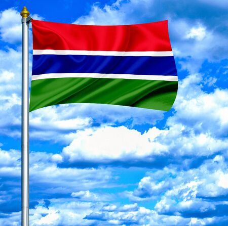 Gambia waving flag against blue sky