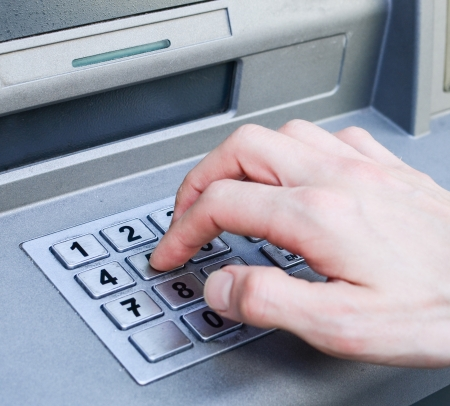 Hand entering PIN numbers on ATM bank machine Stock Photo - 14058926