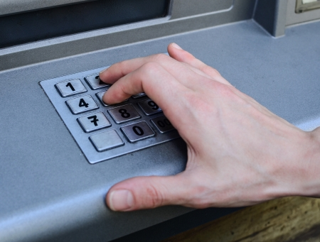 Hand entering numbers on ATM machine photo