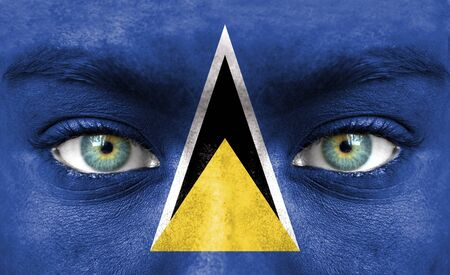 saint lucia: Human face painted with flag of Saint Lucia Stock Photo