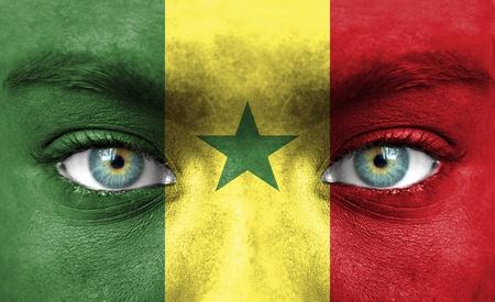 Rostro humano pintado con la bandera de Senegal Foto de archivo - 14256405