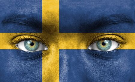 Human face painted with flag of Sweden photo
