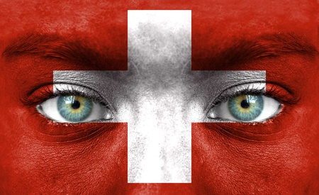 Human face painted with flag of Switzerland photo