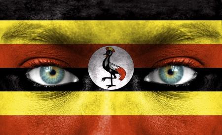 Uganda: Human face painted with flag of Uganda