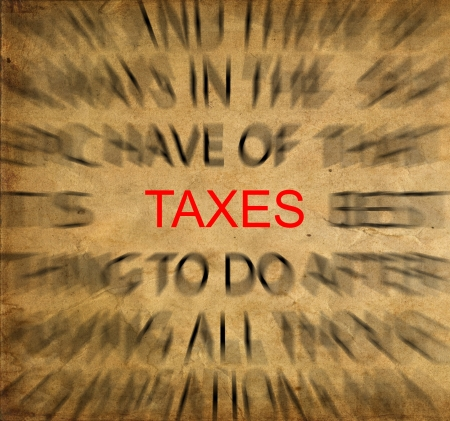 imposition: Blured text on vintage paper with focus on TAXES Stock Photo