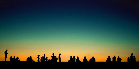 Group of young people sitting on wall at sunset photo