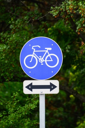 Bicycle sign in park with arrow in both directions photo