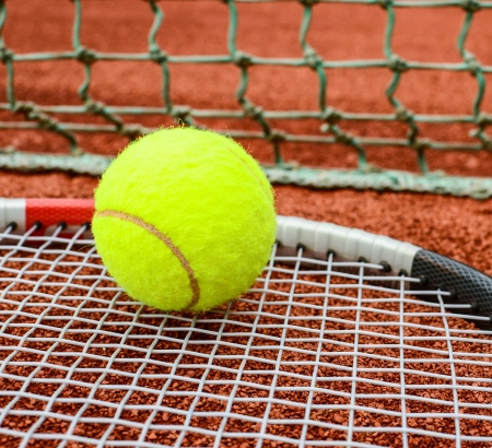Tennis racket with ball on it clay on clay court  photo